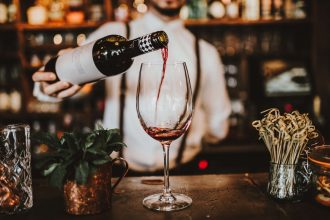 Barman pouring wine into glass