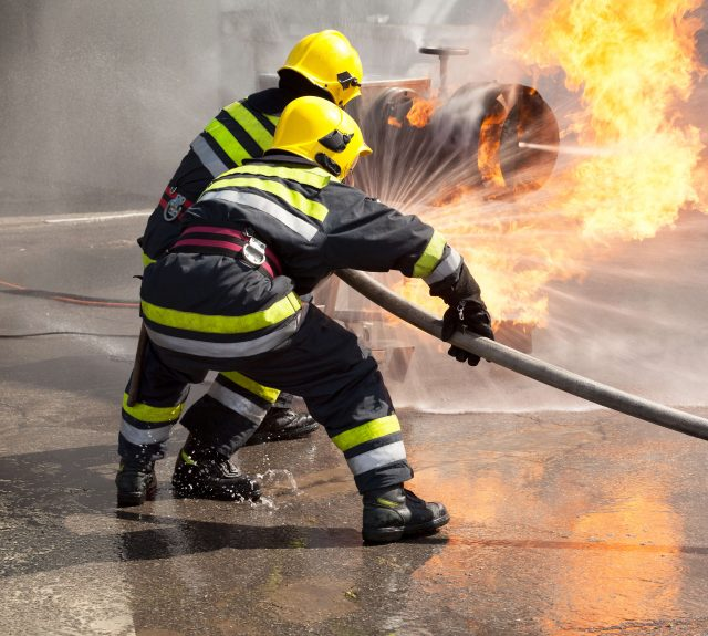 Firefighters putting out fire with hose
