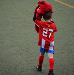 child walking onto football pitch