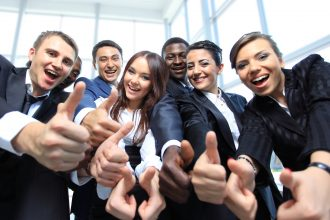 smiling office workers giving thumbs up