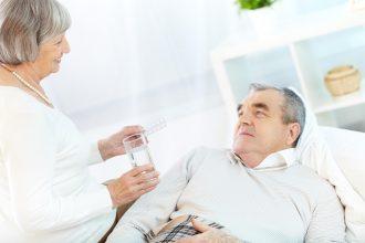 woman handing man pills and water