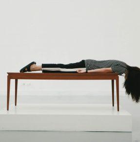 woman lying facedown on table