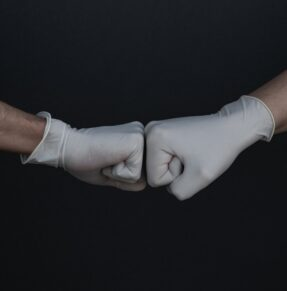 gloved hands fist bumping