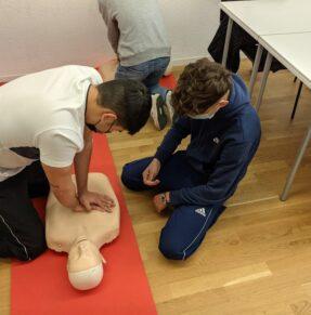 man teaching boy CPR